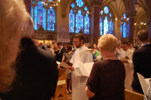 As Mass begins, Chris enters the church as a deacon...