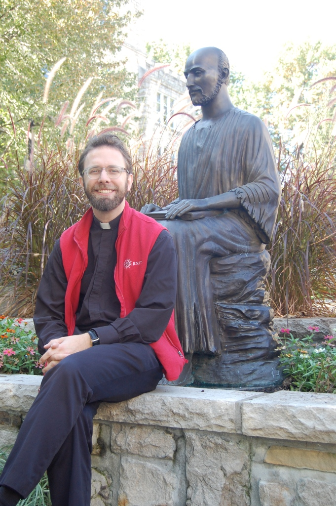 A young Jesuit...alongside a statue of the original Jesuit, St. Ignatius Loyola.